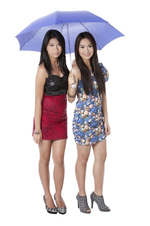 Portrait of two gorgeous ladies sharing an umbrella over a white background Banco de Imagens