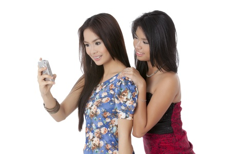 Two beautiful ladies looking at a cellphone and smiling over white background