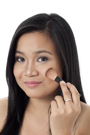 Portrait of a beautiful young woman applying blush to her cheek photo