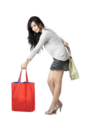 carrying: Portrait of a woman picking up shopping bags while holding her personal bag