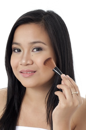Portrait of a Beautiful woman applying makeup with brush on her face looking at camera and smiling against white background photo
