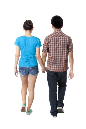 Young couple walking with holding hands in a rear view image