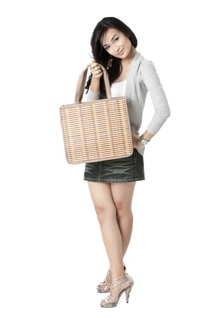 Portrait of a young female holding a bag and showing it to the camera over white background