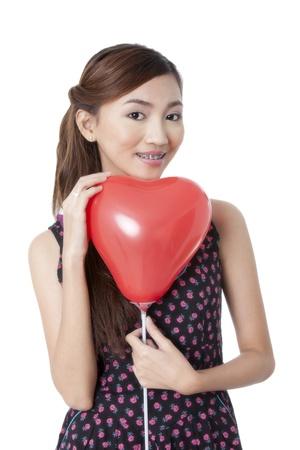 palloncino cuore: Close up immagine di un giovane bella asiatica in possesso di un palloncino rosso cuore e di fronte alla telecamera