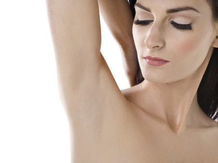 Portrait of woman looking to her clean armpit against white background photo