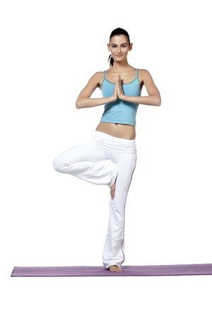 Portrait of a young woman standing with one foot on a mat performing yoga exercise