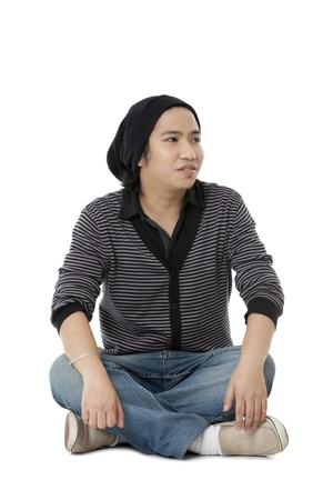 pinoy: View of a boy in casual wear and wearing skull cap sitting on floor. Model: Jomarie Nepomuceno Stock Photo