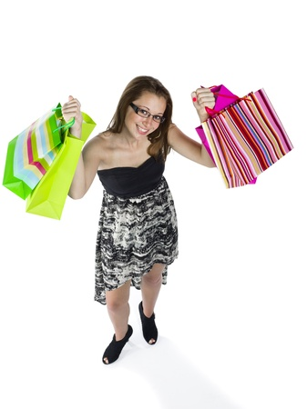 Portrait of a happy teenage girls holding up shopping bags against white background. photo
