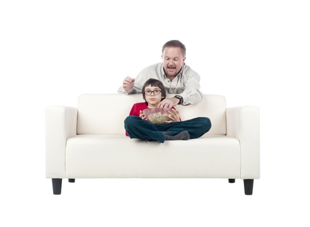 Father and Son on a sofa watching and eating pop corn Stock Photo - 17492818
