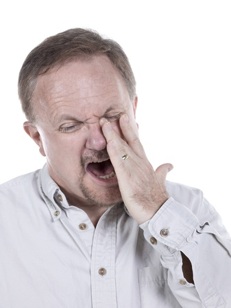Portrait of an old man crying over his sinusitis on a white background photo