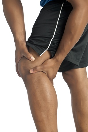 Cropped image of a dark man suffering from knee pain isolated on a white surface