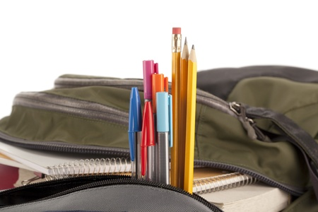 school bag: Materiales escolares en una mochila abierta