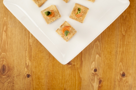 Top view image of smoked salmon on crackers placed on white plate