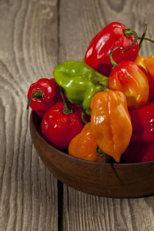 Cropped image of a bowl of hot bell peppers on a wooden table Imagens