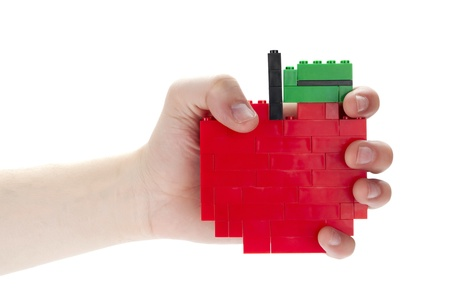 Close-up image of a humans hand holding an apple made of blocks