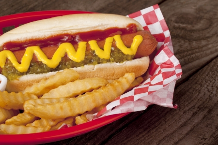 cropped image: Cropped image of a red plate with hotdog sandwich and potato fries on a wooden table