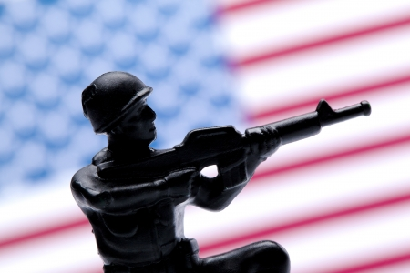 plastic soldier: Closed up shot of an American soldier over a blurred American flag background