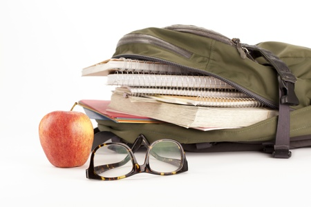 educational tools: Cropped image of backpack with school supplies and apple on the side of a white surface