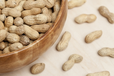 monkey nuts: Bowl of organic peanuts with scattered peanuts on the table
