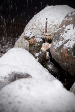 plastic soldier: Close up image of brave toy soldier on snowy rock battlefield