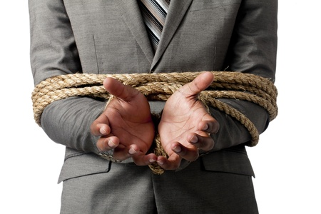 Close-up image of businessman hands tied with rope against the white surface Stock Photo
