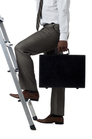 Cropped image of a businessman with briefcase climbing ladder over the white background Zdjęcie Seryjne