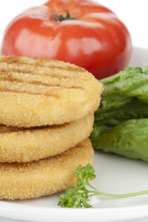 Cropped image of cooked chicken patties with lettuce and tomato