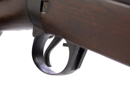 A close up image of a trigger of an old gun against white background