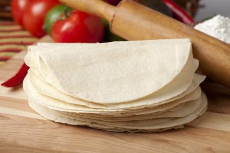 tortilla de maiz: Imagen del primer de una pila de papel de tortilla vac�a en la mesa de madera
