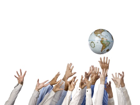 Image of a human's hand reaching the globe on a white surface