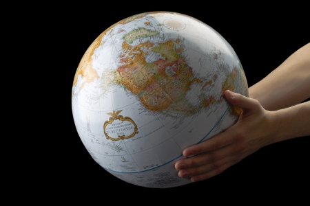 Close-up image of a human hand holding world isolated on a dark surface