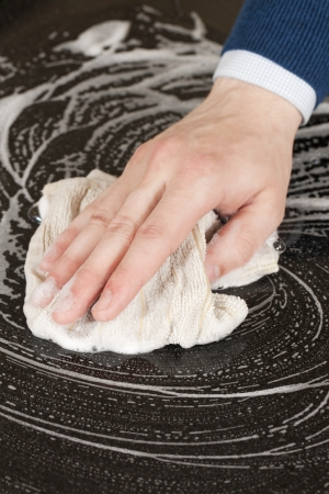 Closeup shot of a male hand wiping a ceramic furniture using a soapy cloth photo