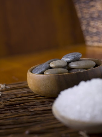 Herbal salts and spa stones placed in a wooden bowl photo
