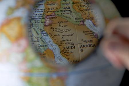 Close up image of magnifying glass focusing the Saudi Arabia map