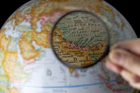locating: Close up image of magnifying glass in front of Himalayas map Stock Photo