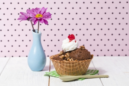 eis: Nutty chocolate ice cream in a big cone with whipped cream and cherry toppings served with napkin and spoon beside a base with flowers