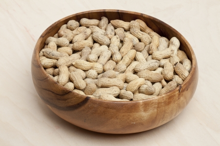 Image of organic peanuts on wooden bowl placed on wooden table