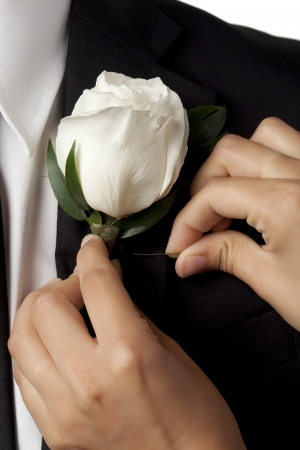 graduation suit: Placing white flower on black graduation suit in a cropped image Stock Photo