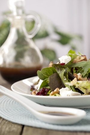 worcestershire: Low angle shot of plate of salad beside a spoon and bottle of Worcestershire sauce Stock Photo