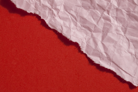ripped: Close up image of ripped pink paper against red background Stock Photo