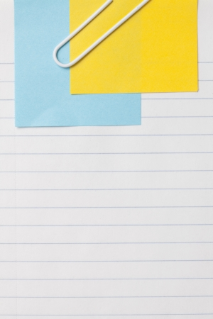 Close up image of sheet of paper with adhesive note and paper clip against white background photo