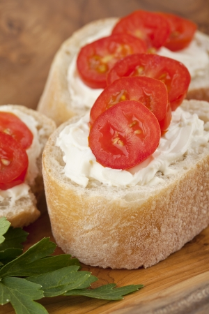 bakery products: Close up image of slices of baguette bread with butter spreads and tomato slices