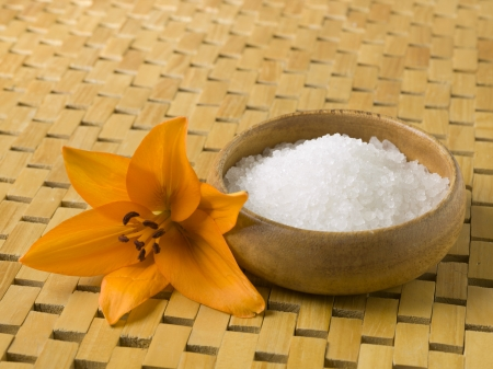 Close-up image of spa salt on a wooden bowl and yellow flower Reklamní fotografie
