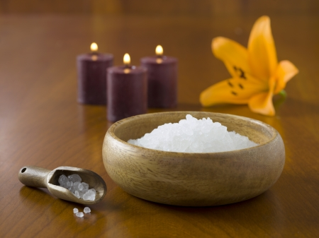 Close-up image of spa salt with candles and flower on the wooden table photo
