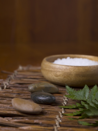 Spa stones and a bowl of herbal salt placed on top of a bamboo table photo