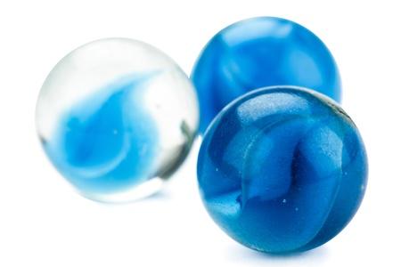 round glasses: De cerca la imagen de tres canicas azules sobre fondo blanco