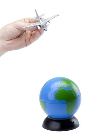 Human hand playing Miniature military jet landing on the globe