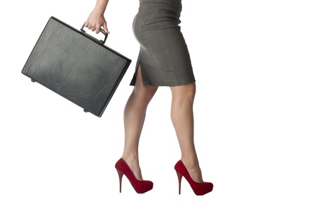 Cropped walking businesswoman while carrying a suitcase over the white background Stock Photo - 17485993
