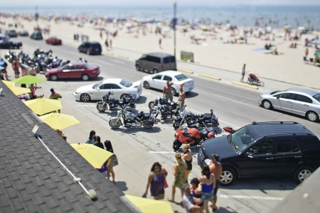 High angle view of cars and bikes in parking lot with beach in background.