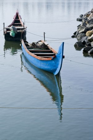 Two boats are tied to the rocks on the coast of Arthungal, India